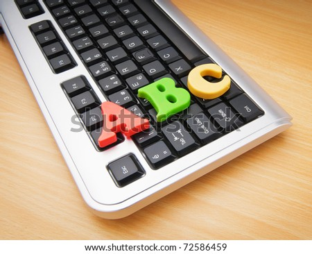 Early education concept with keyboard and letters - stock photo