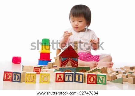 "Early education concept with little girl playing behind the alphabet block arranged to form 'EDUCATION"". *** Main focus on EDUCATION word block ***"