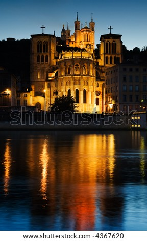 Early evening picture of the Notre Dame de Fourviere basilica and the St. Jean cathedral both illuminated and reflected on the waters of the river Saone, in Lyon, France - stock photo