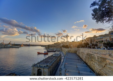 Early evening sunset HDR photo of the Valetta harbor with decorative light beams - stock photo