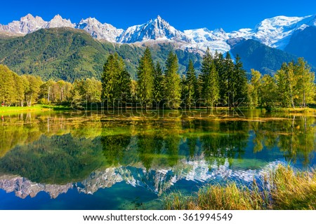 Early fall in Shamoni,  France. The snow-covered Alps and evergreen fir-trees are reflected in lake - stock photo