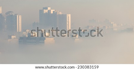Early foggy morning over the city.  Dense fog envelops the residential area. Buildings sticking out of the fog. - stock photo