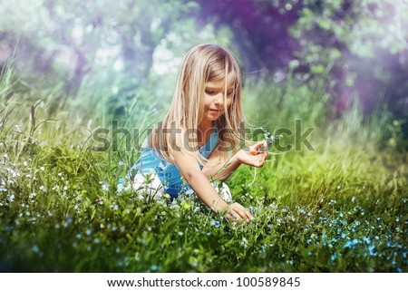 Early in the morning, cute little girl sitting on his haunches in a meadow holding a flower, picking blossom makes a bouquet. A child enjoys life. - stock photo