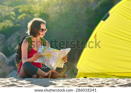 Early in the morning young woman tourist sit near the tent reading the map and thinking about future walking tour.Traveling along Asia, freedom and active lifestyle concept - stock photo