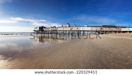 Early morning at Old Orchard beach, Maine, USA. Panorama showing the old wooden pier, sea and sand before the arrival of the daily crowds. - stock photo