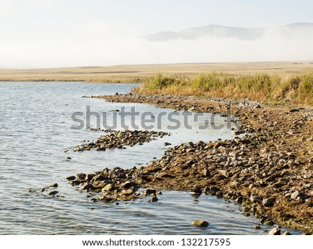 Early morning at the lake with fog in early Fall. - stock photo