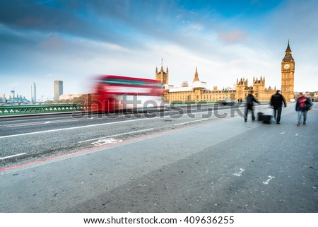 early morning at Westminster Bridge in London , bus in motion and people walking - stock photo