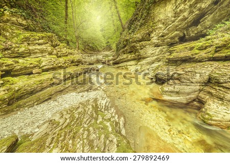 Early morning by the creek with clear water in the deep canyon. - stock photo