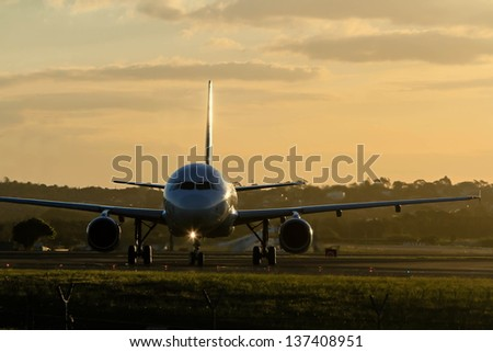 Early morning commercial jet airliner on runway - stock photo