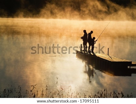 Early morning fishing in autumn on a lake as the mist rises from the water. - stock photo