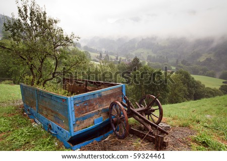 Early morning fog in the Swiss Alps - Vintage Swiss farm carriage and wheels located in the Prattigau Valley of the city of Saas in the Graubunden canton of Switzerland.