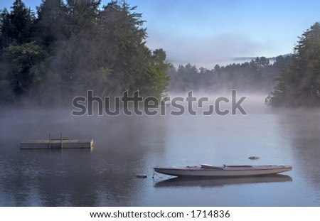 Early morning fog on a lake. A boat and dock are in the foreground. - stock photo