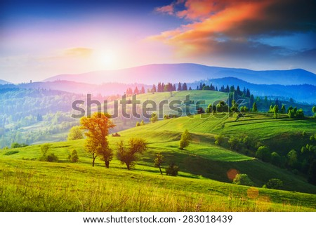 Early morning in a Carpathian valley with green meadow and colorful clouds in beautiful light of sunrise - stock photo