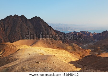 Early morning in ancient mountains of Sinai desert. Sunrise over Red sea - stock photo