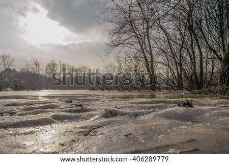 Early morning in the forest. Forest lake covered with ice. The rays of the sun and colorful clouds.Spring landscape.Spring flood. Bottom view on the snow and ice on the river.The thaw in early spring.