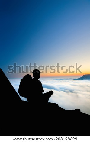 Early Morning in the mountains and clouds with fog in the valley. Tourist sitting on top of the mountain and meets sunrise - stock photo