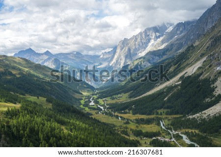 Early morning in Val Ferret valley in Italy, with overcast sky and rocky mountain range - stock photo