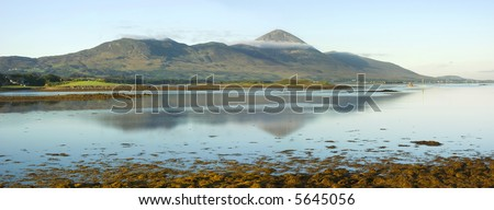 Early morning light of a September dawn strikes the misty slopes of Croagh Patrick, Co Mayo, Ireland and illuminates the little church at the summit, goal of an annual pilgrimage by the faithful. - stock photo