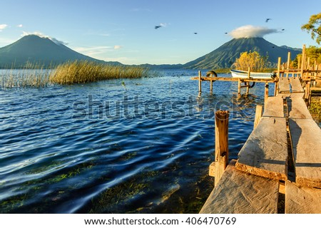 Early morning light on three volcanoes: Toliman volcano (Atitlan volcano behind) & San Pedro volcano on Lake Atitlan, Guatemala. Photo taken from Santa Cruz la Laguna. - stock photo