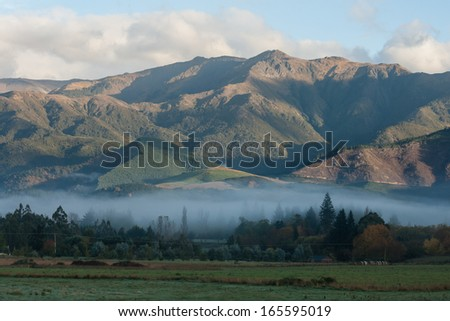 early morning mist above Hanmer Springs - stock photo