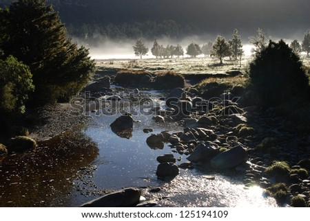 Early morning mist on a river in New Zealand - stock photo