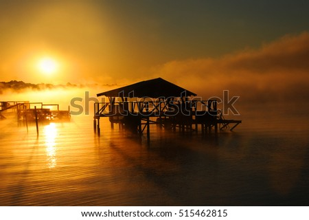 Early morning mist rises from Lake Chicot in Lake Village, Arkansas.  Wooden dock and boat house are silhouetted. Golden light covers lake.