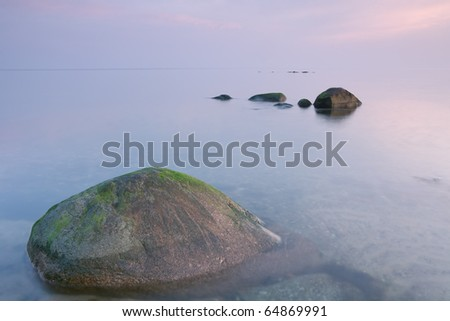 Early morning on the Baltic Sea, captured by the quiet and calm water at sunrise in the background of delicate colors. - stock photo