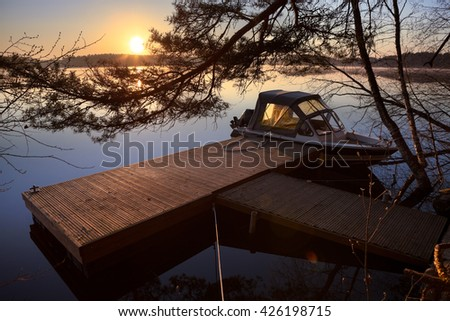 Early morning on the lake shore with speedboat moored to the pier - stock photo