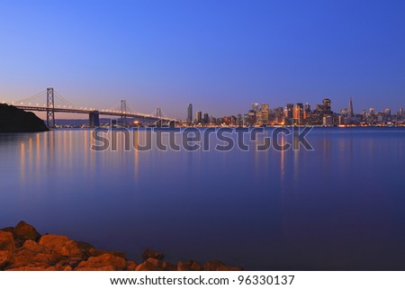 early morning photo of San Francisco and the bay bridge blue calm water and sky - stock photo