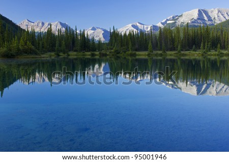 early morning reflections of mountains and trees in Forgetmenot Pond
