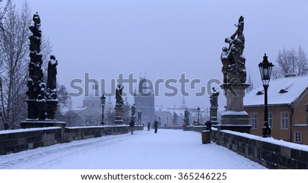 Early Morning romantic snowy Prague Old Town with Bridge Tower and St. Francis of Assisi Cathedral from Charles Bridge with its baroque Statues, Czech republic - stock photo