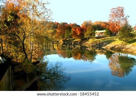 Early morning sky is reflected in the still waters of a Northern Arkansas river.  Autumn colors trees and leaves.  Home sits on waters edge. - stock photo