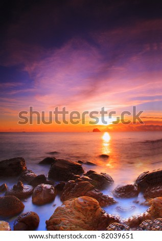 early morning sun rise over the coast with beautiful cloud and sky - stock photo