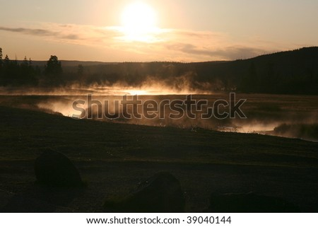 Early morning sun shining through the mist rising from a river winding through grass land in Yellowstone National Park. - stock photo