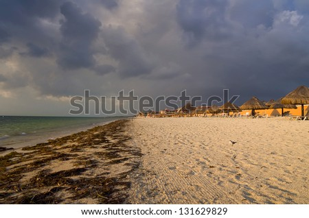 Early morning sunlight bathes Cancun Beach with ominous clouds overhead - stock photo