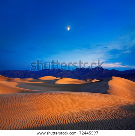 Early Morning Sunlight Merges With A Twilight Moon Over Sand Dunes And Mountains At Death Valley National Park, California, USA - stock photo