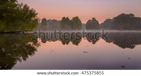 Early morning sunrise scene of pond and trees in park Stadspark Groningen, The Netherlands