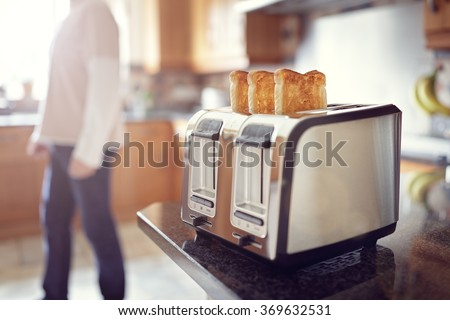 Early morning toasted bread, man in the kitchen preparing toast for breakfast at sunrise - stock photo