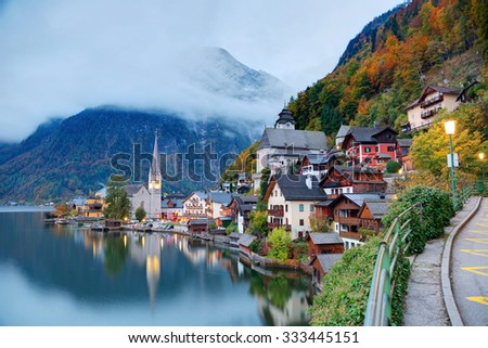 Early morning view of Hallstatt with reflections on smooth lake water, a charming lakeside village in Salzkammergut region of Austria, in colorful autumn season ~ A beautiful UNESCO heritage site - stock photo