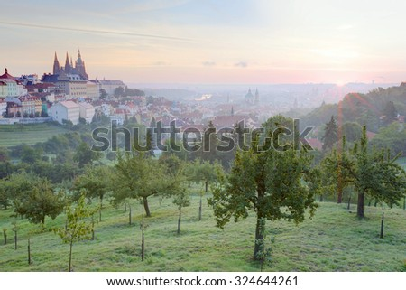 Early morning view of Prague with golden sunrise ~ A panorama over Prague Old Town with majestic Prague Castle and St. Vitus Cathedral on the left and a golden rising sun in the background - stock photo