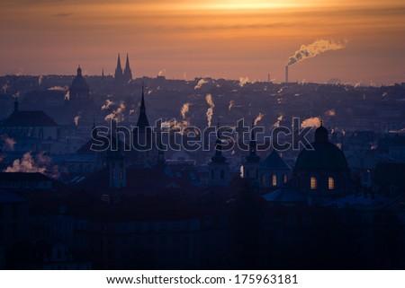 Early morning view of winter Prague city full of smoking chimneys - stock photo