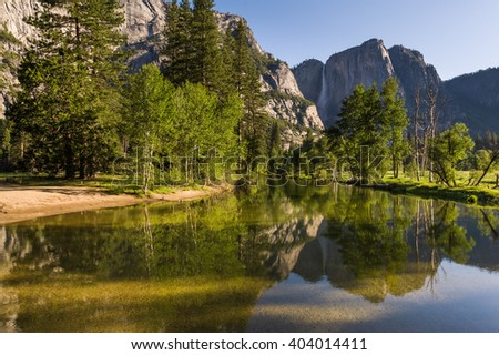 Early morning view of Yosemite Falls with reflection in river.