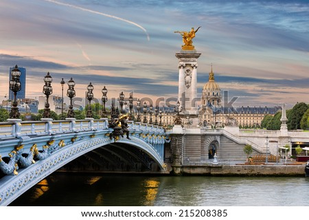 Early morning view on the famous landmark Alexander iii bridge in Paris, capital of France, with beautiful clouds in the sky and the golden statue catching the first sunrays - stock photo