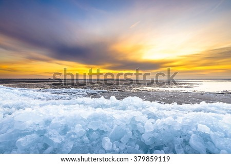 Early morning winter landscape with sunrise and drifting ice floats near costline in the Netherlands - stock photo