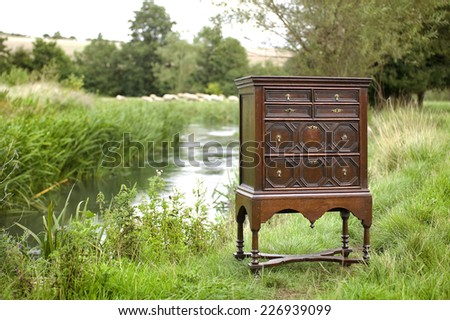 early old antique chest on stand mahogany by the river - stock photo