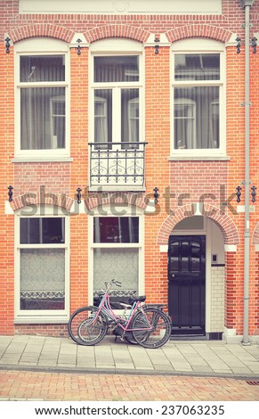 Early 1900s building in Amsterdam, the Netherlands, as an example of Dutch typical vintage urban architecture. Filtered toned image in a retro nostalgic style.  - stock photo
