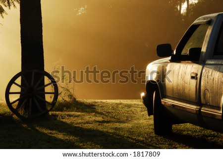 Early September morning in rural Tennessee.  Very foggy with sun-rays striking the pickup truck that is covered with heavy dew.  A very calm serene scene. - stock photo