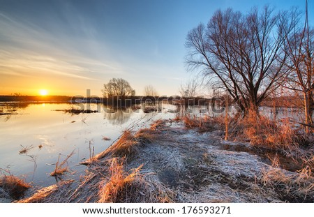 Early spring landscape. Sunrise on a flooded river with thawed ice. - stock photo