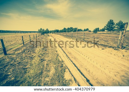 Early spring landscape with farm and rural road, cross process vintage photo - stock photo