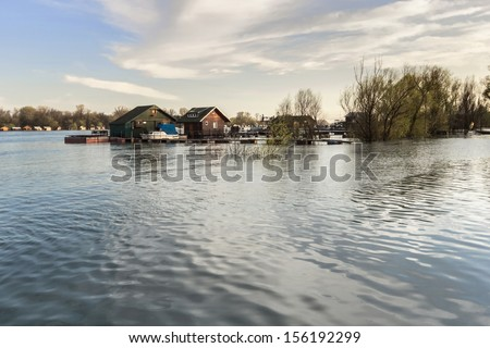 Early spring photograph shot at dusk of risen Sava river water level, with floating houses along its banks, leafless trees canopies, and blue skies with fluffy white clouds. - stock photo
